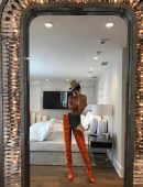 """In the picture, Kendall pairs jeans with waist-high orange boots, a hat, and literally nothing else. Kendall captioned the picture, """"Playing dress up."""""""